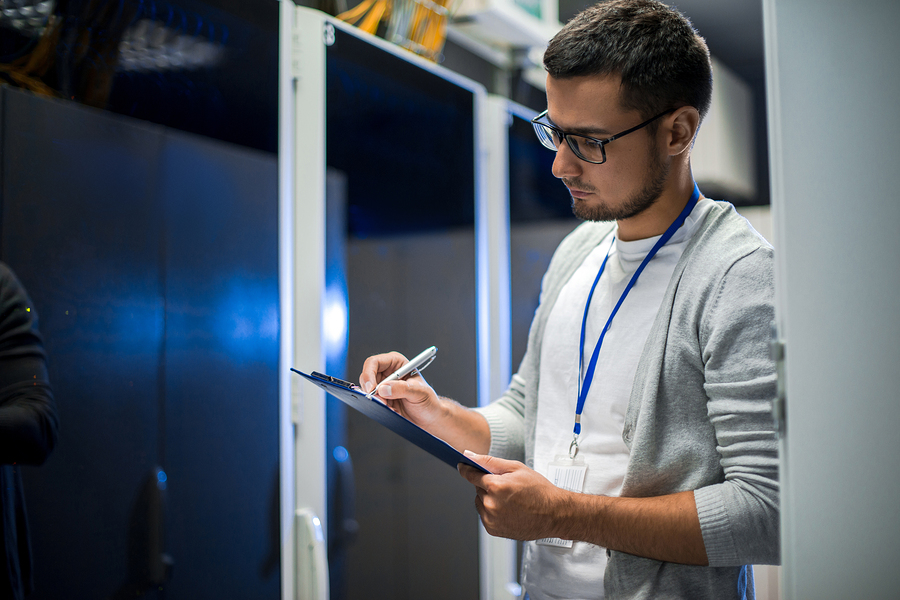 Side view portrait of young network engineer writing data on clipboard while working with servers in data center